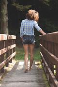 Rear view of gorgeous brunette walking on bridge Stock Photos