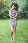 Gorgeous unsmiling brunette walking on grass Stock Photos