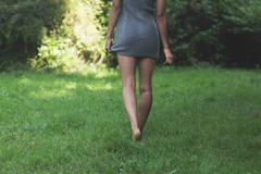 Rear view of lower body of model walking on grass holding dress Stock Photos