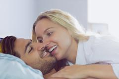 Intimate attractive couple lying on their bed - stock photo