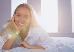 Happy young woman lying on her bed Stock Photos