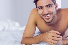 Handsome man lying on his bed Stock Photos