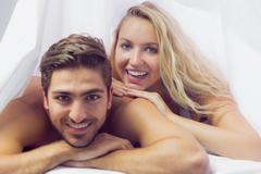 Smiling young couple lying under a blanket - stock photo