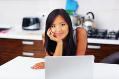 happy young asian woman talking on phone at home - stock photo