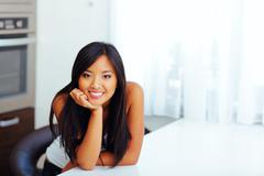 happy beautiful asian woman leaning on hand in her kitchen - stock photo