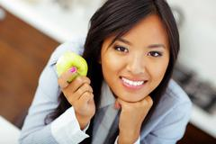 Portrait of a young asian businesswoman holding an apple Stock Photos