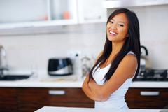 young laughing asian woman with arms folded at home - stock photo