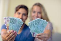 Stock Photo of Cheerful couple showing money