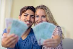 Happy couple showing some money Stock Photos