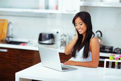 young beautifu asian woman with laptop at home - stock photo