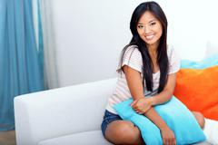 Happy asian woman in casual clothings sitting on the sofa at home Stock Photos