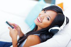 closeup portrait of a young asian woman in headphones listening to music with - stock photo