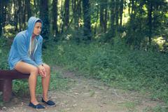 Young casual woman sitting on a bench in a forest Stock Photos