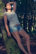 Gorgeous ponytailed woman posing leaning against a tree Stock Photos