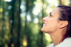 Stock Photo of Gorgeous natural woman sitting in a forest