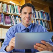 Handsome librarian sitting at desk using tablet Stock Photos