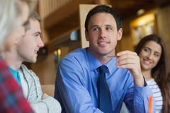 Happy lecturer explaining something to group of students - stock photo
