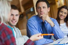 Focused lecturer explaining something to group of students - stock photo