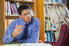 Lecturer explaining something to blonde student - stock photo