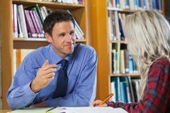 Smiling lecturer explaining something to blonde student Stock Photos