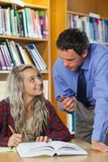 Lecturer explaining something to blonde smiling student - stock photo