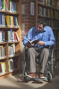 Focused man in wheelchair reading a book - stock photo