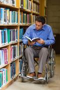 Concentrating man in wheelchair reading a book - stock photo