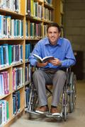 Happy man in wheelchair holding a book - stock photo