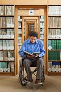 Attractive man in wheelchair reading a book - stock photo