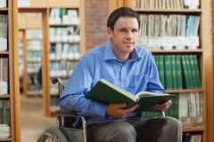 Content man in wheelchair holding a book Stock Photos