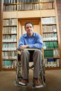 Lucky man in wheelchair holding a book - stock photo