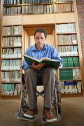 Calm man in wheelchair holding a book Stock Photos