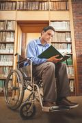 Focused man in wheelchair looking at a book - stock photo