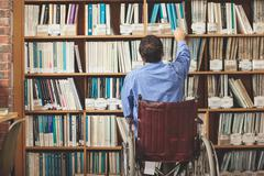 Man in wheelchair taking a book out of bookshelf Stock Photos