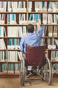 Man in wheelchair putting back a book in bookshelf - stock photo