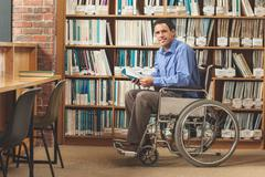 Happy man sitting in wheelchair holding a book - stock photo