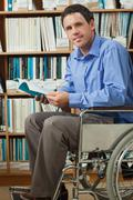 Smiling man sitting in wheelchair holding a book - stock photo