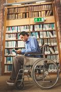 Frowning man sitting in wheelchair reading a book - stock photo