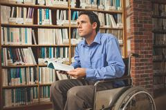 Thoughtful man sitting in wheelchair holding a book - stock photo
