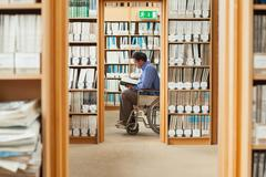 Man sitting in wheelchair reading a book - stock photo