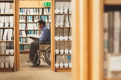 Man sitting in wheelchair looking at a book - stock photo