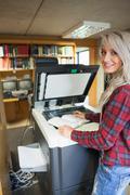 Smiling blonde student using photocopier Stock Photos