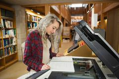 Focused blonde student standing next to photocopier - stock photo