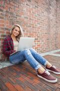 Happy gorgeous student leaning against wall using laptop - stock photo