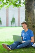 Stock Photo of Cheerful handsome student sitting under tree using laptop