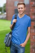 Happy handsome student leaning against wall - stock photo