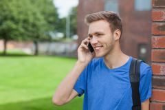 Smiling handsome student leaning against wall phoning - stock photo