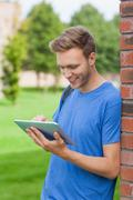 Content handsome student leaning against wall using tablet - stock photo
