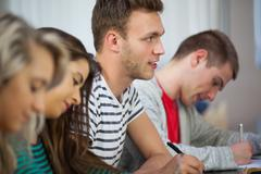 Casual attentive students taking notes - stock photo