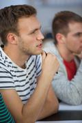 Frowning handsome student looking away - stock photo